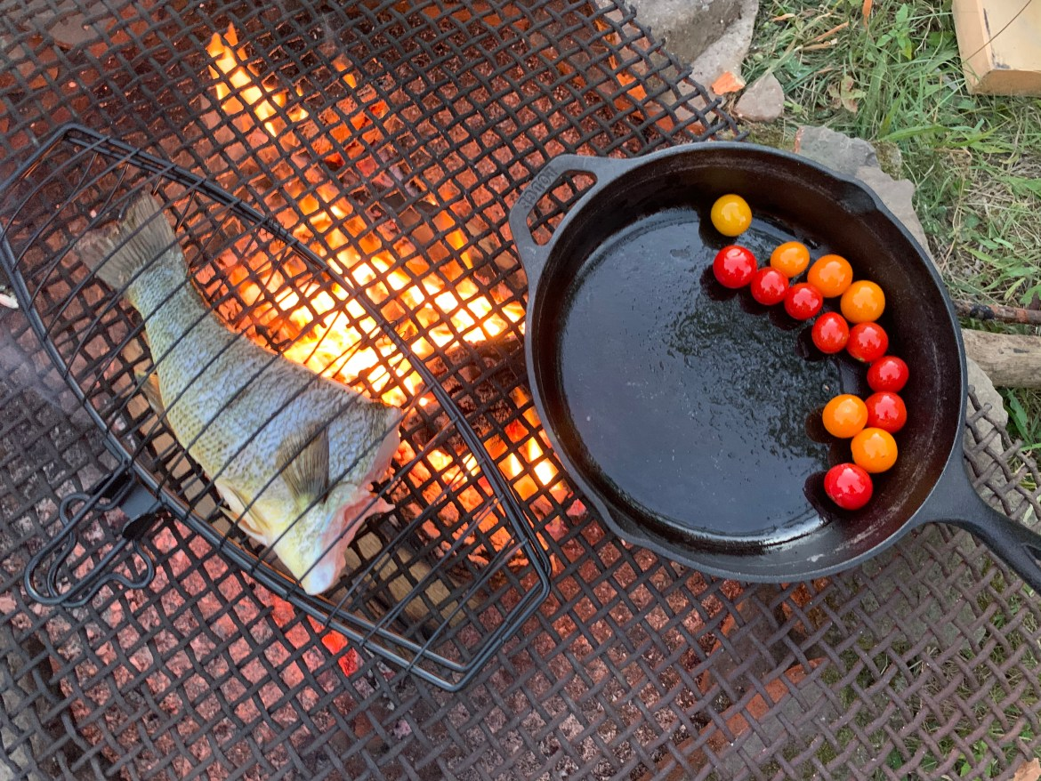 Cleaned and scaled largemouth bass grilled over an open flame, and some sweet cherry tomatoes being sautéed in oil. (Benjamin Velani / Sun Dining Editor)