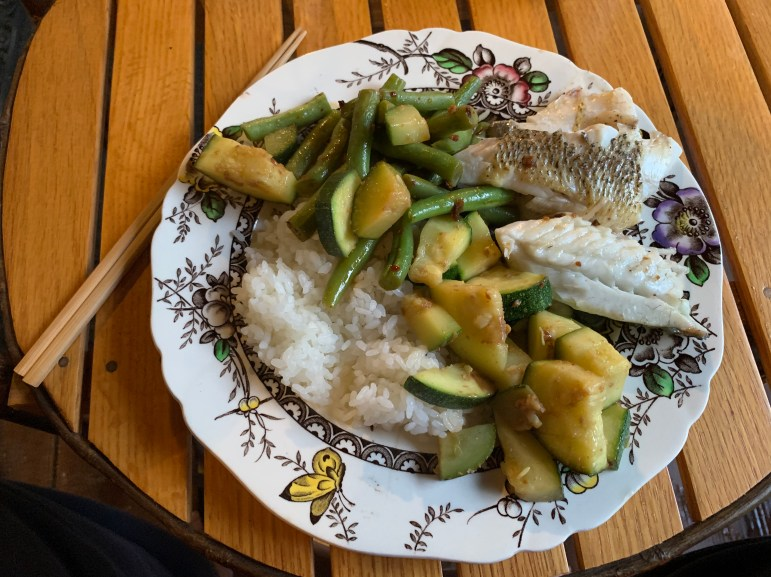 Steamed largemouth bass with sautéed zucchini and beans over rice. (Benjamin Velani / Sun Dining Editor)