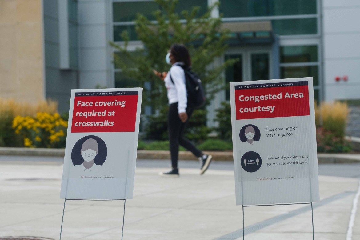 A student traverses campus on the first day of classes. While mask-wearing and biweekly surveillance testing are a few of the reasons for Cornell's minimal new case count, peer ambassadors are another reason, who have modeled the University's public health guidelines.