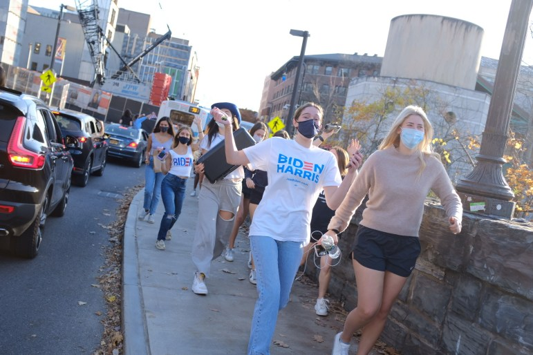 Students skip down the Collegetown sidewalk on Saturday as they celebrate the Biden-Harris win.