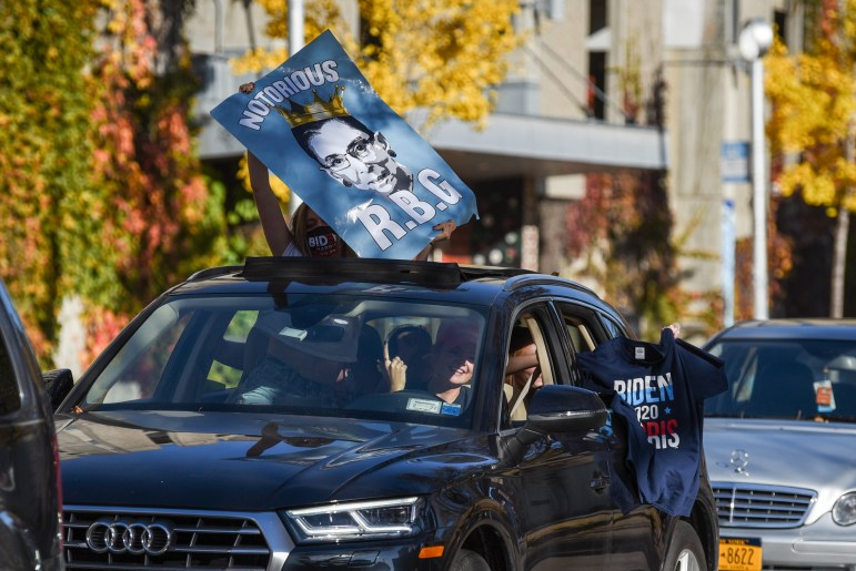 """Students showed off """"Fuck Trump"""" signs and Biden shirts through sunroofs to whoops from passersby in Collegetown."""