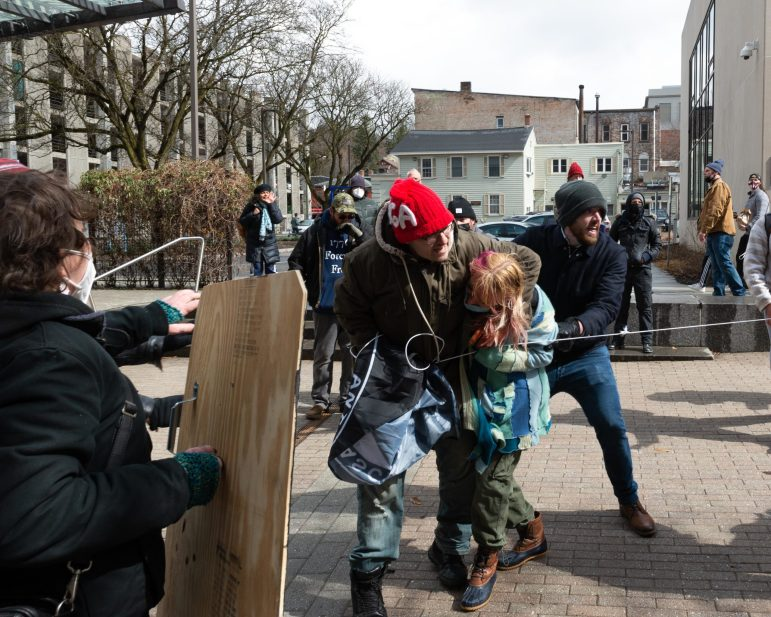 Protesters engage in a physical altercation as others try to break up the fight.