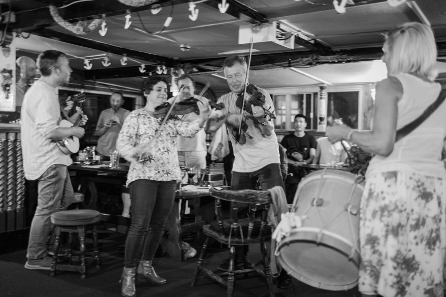 Black and white photograph by Lee J Palmer of musicians playing at the Admiral Benbow pub showing two fiddlers, mandolin player and drummer and audience looking on.