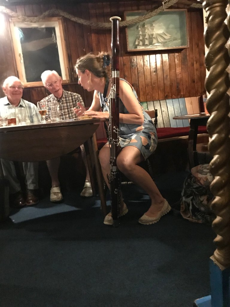 Women holding a bassoon between her knees at the Admiral Benbow pub.