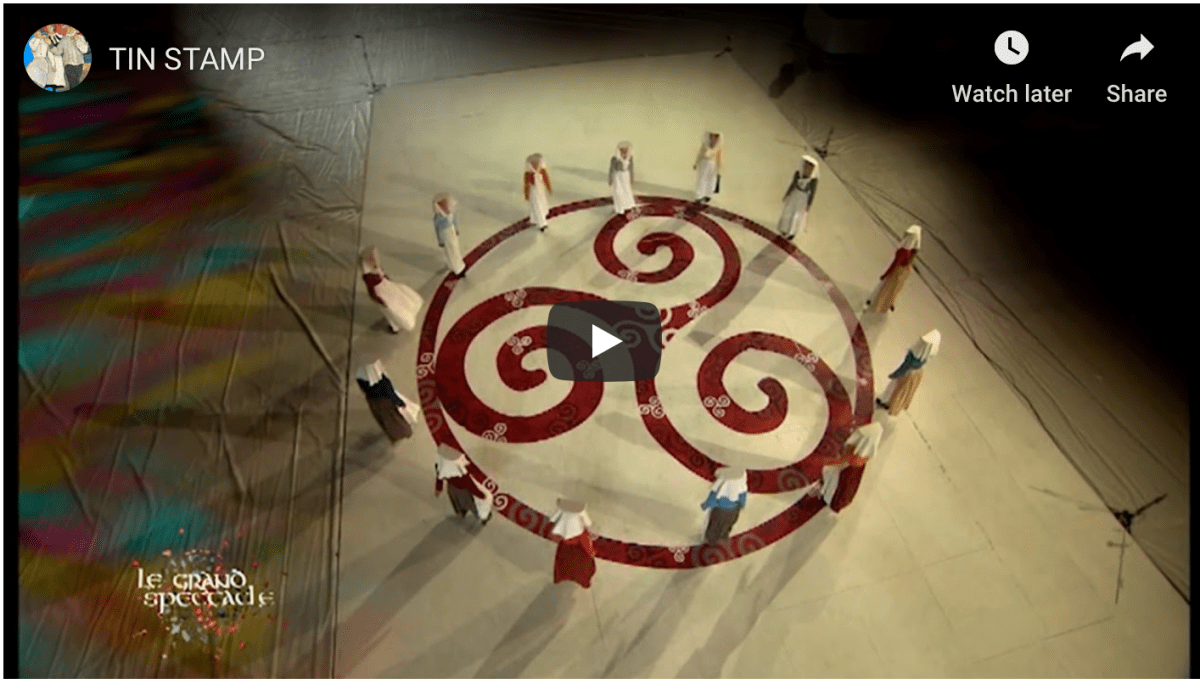 Screenshot of Tin Stamps video showing Cornish dancers in a large circle around a triskele. Dancers (female) wearing traditional Cornish work wear.