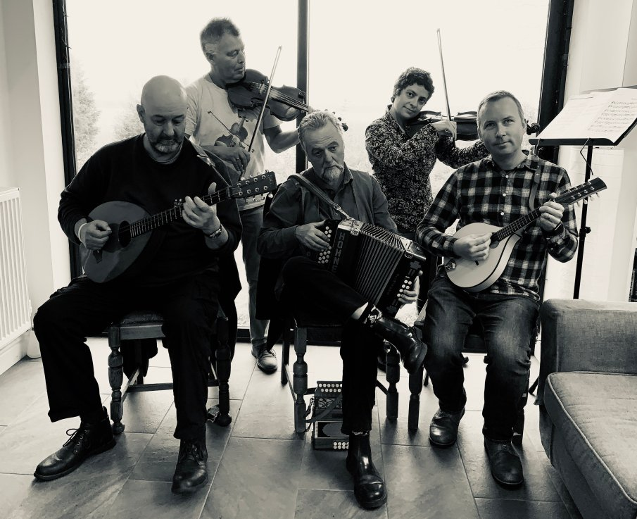 Money to the Moon musicians posing for photograph. Left to right: Pete London (bouzouki), Andy Law (fiddle), John Gallagher (melodeon), Tehmina Goskar (fiddle), Tom Goskar (mandolin).