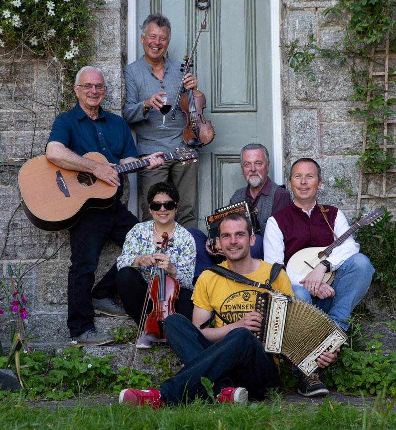 Group photo of Andy Law and Friends featuring Andy Law with fiddle, John Gallagher with melodeon, Tom Goskar with mandolin, Marc Cragg with melodeon, Tehmina Goskar with fiddle and Dave Higginbotham with guitar