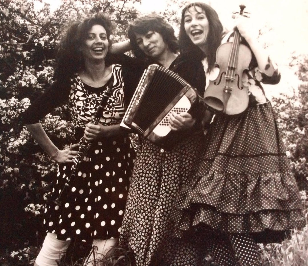 Sepia image of three women in polka-dot and flower pattern outfits holding instruments.