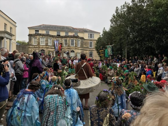 Large gathering, many with flowers in their hair, performers dressed up as sea creatures, St Piran in a monk's habit with a mill-wheel around his waist, a pig hobby horse, banners.