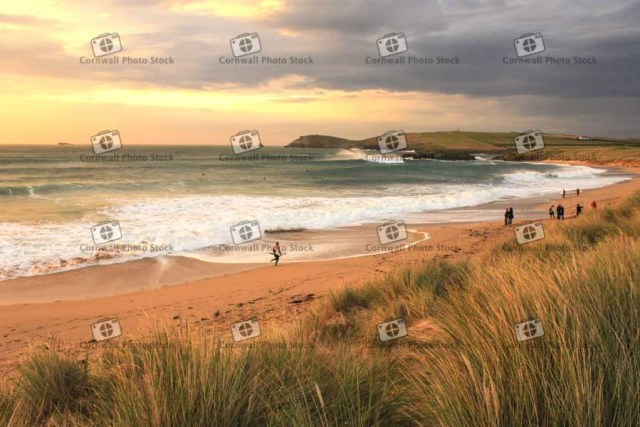 Constantine Beach in Cornwall in the evening sun with waves and surfers