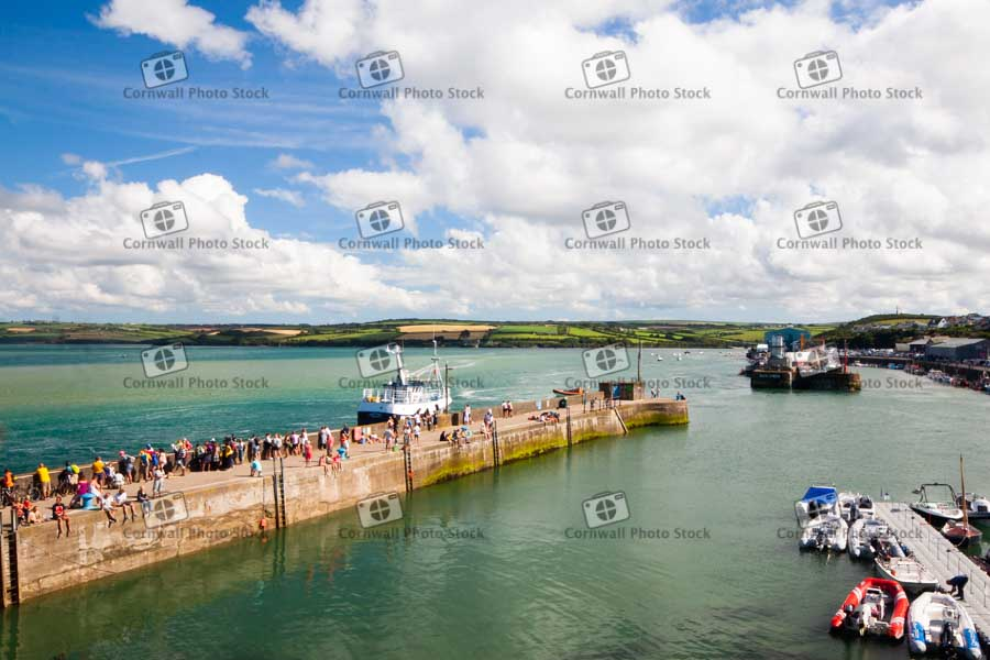 Padstow Harbour Wall With People Relaxing And Fishing Boat