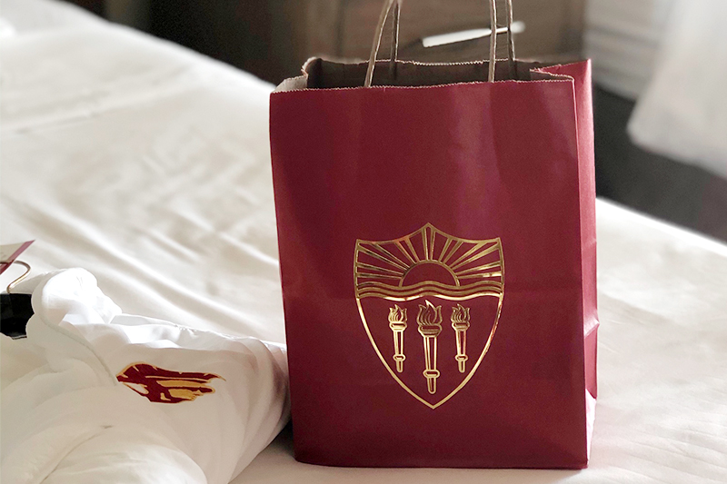 USC care package on a bed at the USC Hotel where accommodations are provided for front line workers