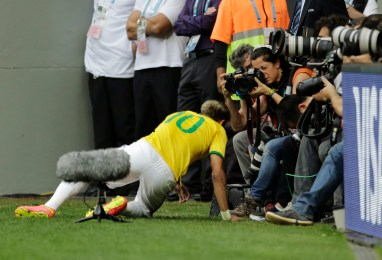 Buenos Aires-based AP photographer Natacha Pisarenko focuses on Brazil's Neymar during the group A World Cup soccer match between Cameroon and Brazil at the Estadio Nacional in Brasilia, Brazil, Monday, June 23, 2014. (AP Photo/Bernat Armangue)