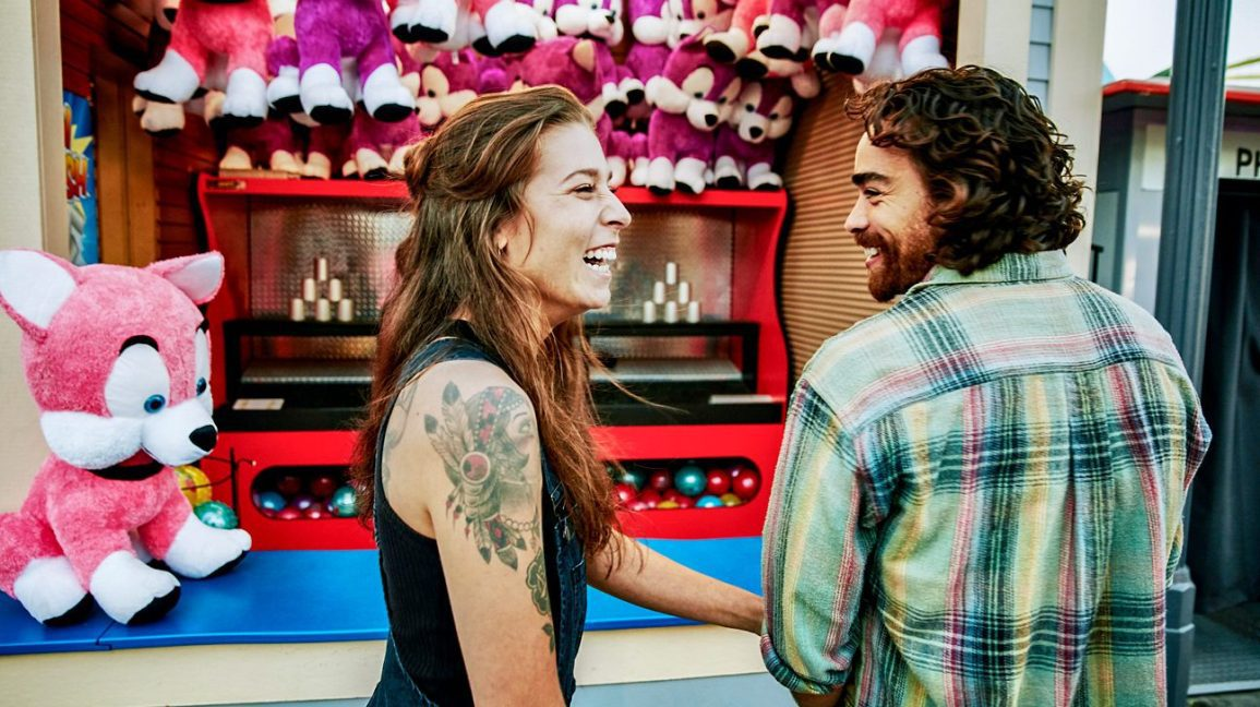 A white woman with brown hair, tattoos on her right shoulder, wearing a black tank top smiles and laughs while looking at her companion, a white man with reddish brown hair, mustache, and beard, wearing a green plaid shirt. They're in front of the milk bottle toss carnival game.