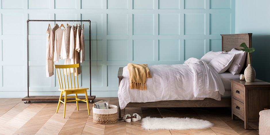 Redecorate and Refresh  Threshold Furniture Collection Doubles in     Light and airy bedroom with blue paneled walls  a wooden bed and nightstand  with white