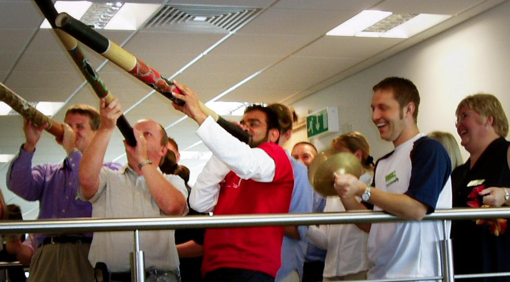 colleagues laughing as three men play didgeridoo in a world music energiser