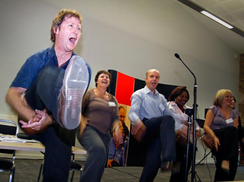 MArk Walker leading a singing activity with participants onstage