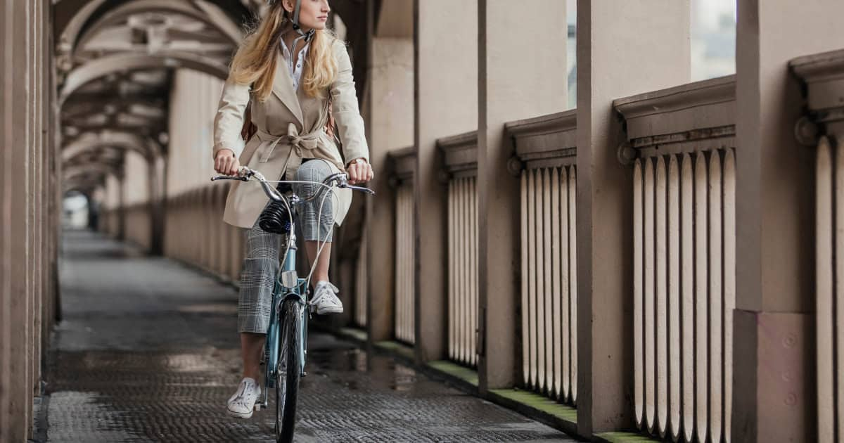 how to commute to work on a bike - image of a stylish young professional woman commuting to work on a bike but still looking polished