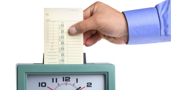 stock photo of a punch clock with a man holding a time card
