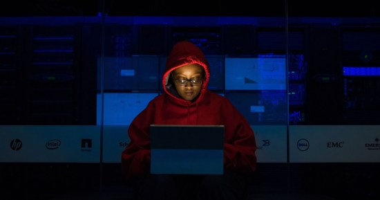 a woman in a red hoodie works in a dark office at a computer