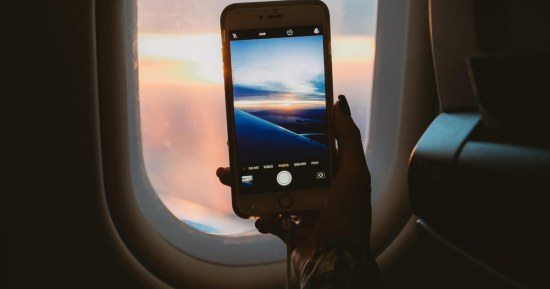 stock photo of woman taking picture out plane window
