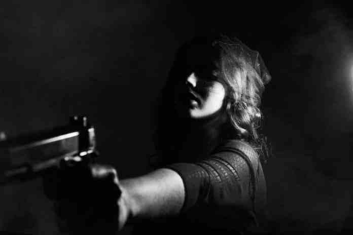 Femme menaçant avec un pistolet