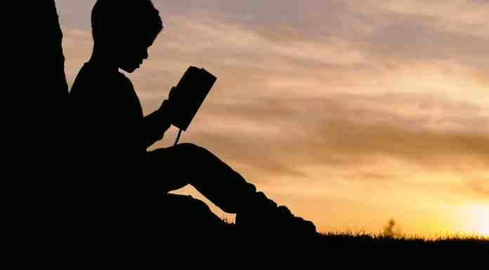 Enfant lisant dans un coucher de soleil