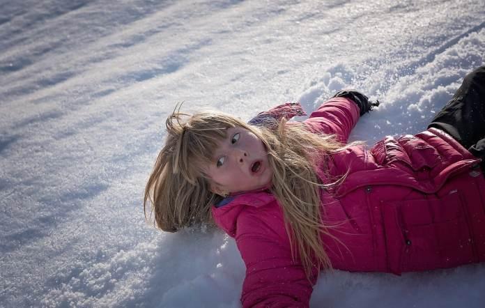 Fille glissant dans la neige