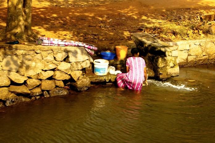 Femme qui lave son linge dans la rivière