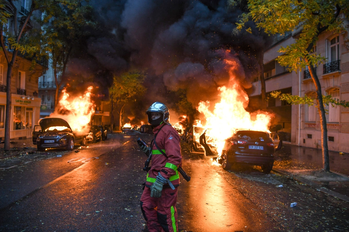 A firefighter looks on as cars are burning during a protest of Yellow vests (Gilets jaunes) against rising oil prices and living costs, on December 1, 2018 in Paris. - Speaking at the Paris police's command centre, French Prime Minister said 36,000 people
