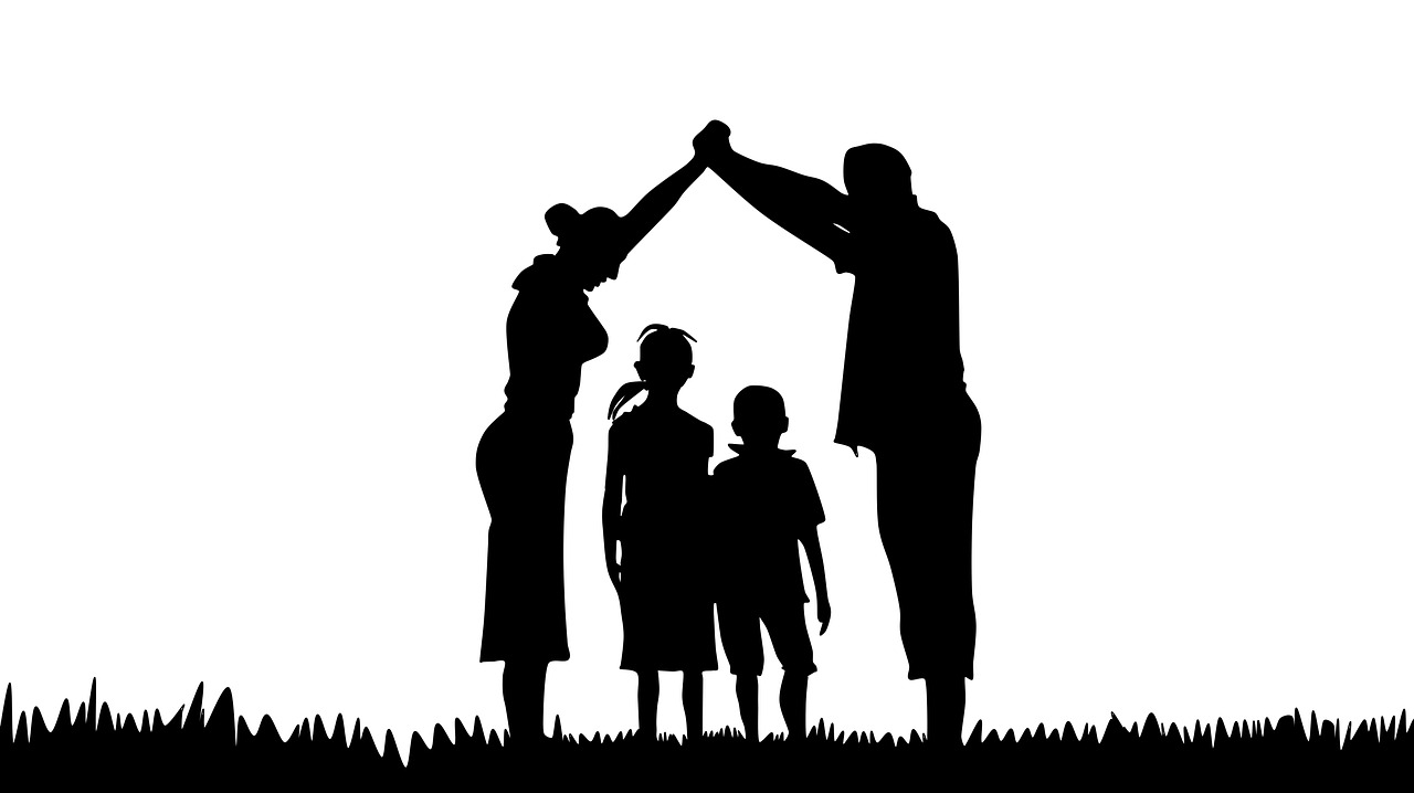 Silhouetted family mother and father making protective arch over children