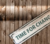 Dilapidated sign hanging from one end reads 'Time for change'