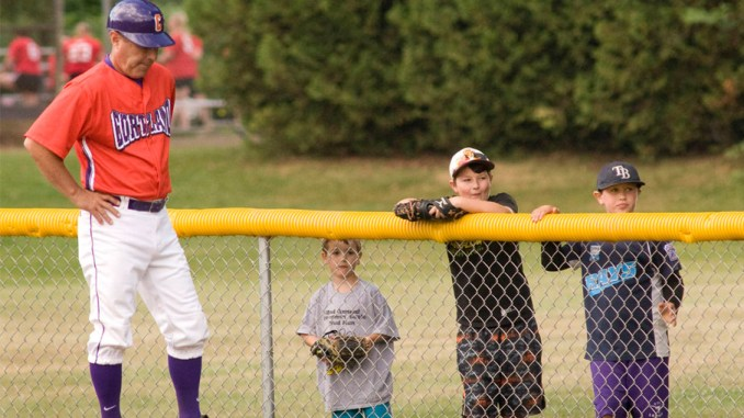 Bob Ellis/staff photographer With school out for the summer, young fans, from left, Evan Rogoff, his brother, Luke, and Caleb Epp watch a Cortland Crush baseball game June 29 at Beaudry Park. Cortland Crush manager Bill McConnell coaches first base.