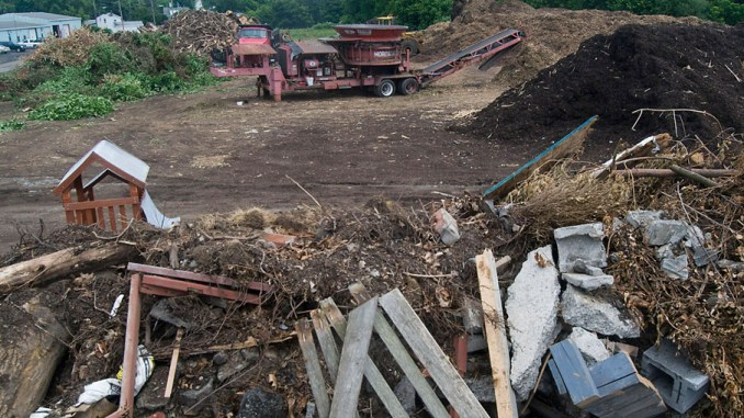 Pieces of concrete, wood and other debris, in foreground, are shown sorted and piled next to ground-up compost at the city's composting area Thursday on South Franklin Street. Cortland Department of Public Works employees regularly sort non-compost material before running it through the large grinding machine (at center in background).