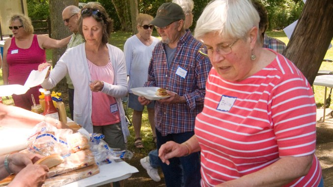 Volunteer Belinda Burtner grills hot dogs Tuesday at a joint picnic with Memory Cafe participants at Durkee Park in Homer.