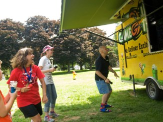 Owen Coon, 7, of Cortland, left, enjoys an ice cream cone while watching a dancing game performed by Cortland Free Library's Youth Services Director Tammy Sickmon, Michaiah Hitchcock and Game Truck Central NY owner Luis Mendez. The party was part of the library's Summer Reading Program Finale party held Saturday at Courthouse Park.