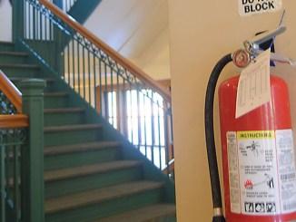 A fire extinguisher is mounted on the wall Tuesday in the lobby of Old Main on the SUNY Cortland campus. The college uses orientation programs to educate students on safe ways to exit buildings and other procedures in responding to fire alarms.