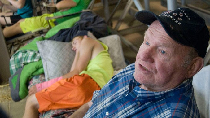 Roland Ripley, 77, relaxes Thursday at the New York State Fair while grandsons Daniel, 17, and Benjamin, 16, take a morning nap. The Ripleys were at the fair showing their Guernseys.