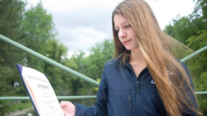 Sailor Tetreault, 16, stands on a bridge over the West Branch of the Tioughnioga River near her home in Homer while holding her Homer High School diploma Wednesday. Tetreault graduated in three years after doubling up on math, English and social studies classes, along with taking 11th- and 12th-grade classes in the same year.