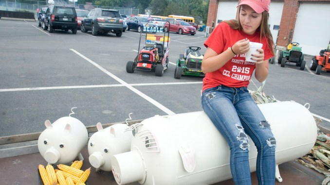 Cincinnatus High School senior Ciara Zeeuw enjoys corn chowder while relaxing on her family's parade float Saturday at the Cinncinatus Corn Festival. The float of a sow with her piglets is made of propane tanks and items found around the farm.