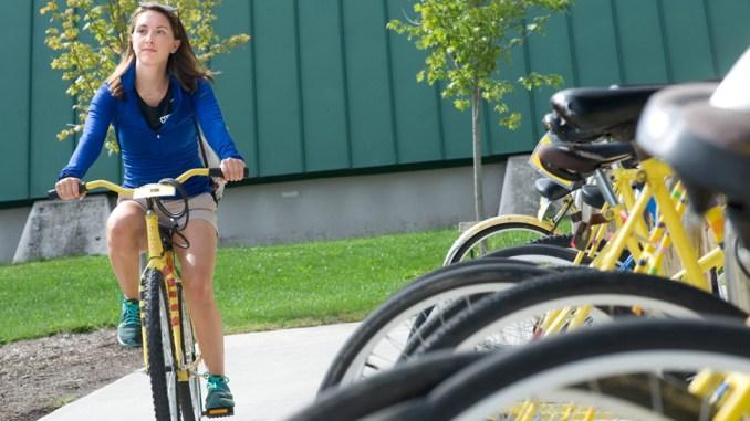 SUNY Cortland senior Kayla Simpson rides one of the yellow university fleet bikes Monday near the Student Life Center in Cortland.