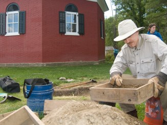 Brant Venables, of SUNY Binghamton, screens soil during an archaeological dig Saturday outside the octagonal schoolhouse in the town of Dryden. The school was in operation from 1827 until the 1940s.