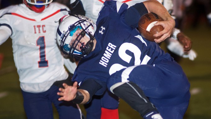 Joe McIntyre/staff photographer Homer Central's John Horner gets upended by Syracuse Tech defenders in the first quarter Friday at Butts Field. Horner scored four touchdowns in a 34-6 romp.