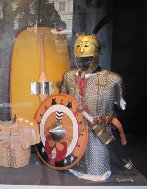 Some of the equipment of a triarius. His spear (hasta) is missing. He would have used the large shield at the back, not the small round shield. His sword is on the wrong side. It was worn on the right.