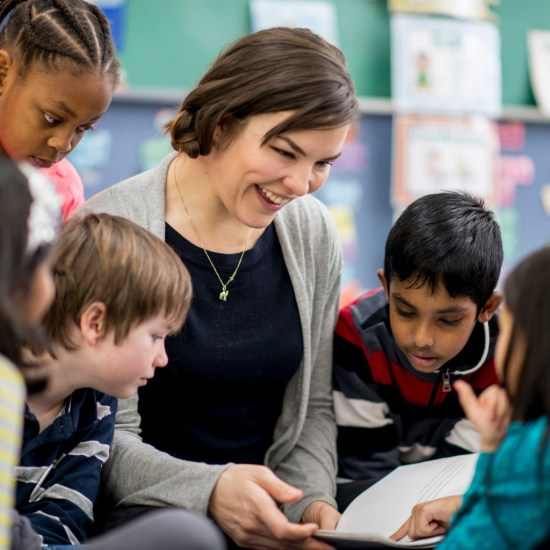Teacher surrounded by students read books