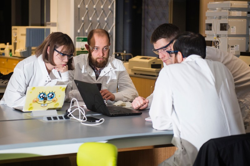 A group of students work around a table in a lab.