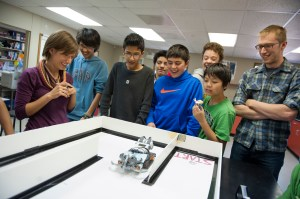 Clint Valentine, right, a third-year biology and environmental science major, right, looks on as 7th and 8th grade science club students from the Buckingham Browne & Nichols school watch a competitor in a robotic lobster competition.