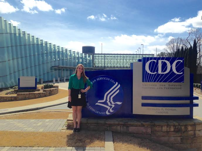 Nina Granow stands in front of the entrance sign at the Centers for Disease Control and Prevention.