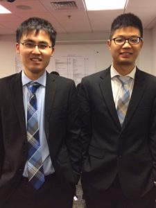 Two students in suits standing side by side