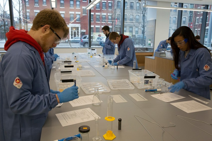 Several students work at a lab bench with large windows behind them.